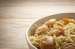 Seafood meal. Freshly cooked meal of prawns and spaghetti served in a white bowl Stock Image