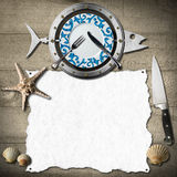 Seafood Menu Background. Restaurant seafood menu with metal fish, plate, fork and knife, seashells and starfish, kitchen knife, empty white paper on a wooden Stock Photo