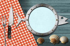 Seafood Menu with Metal Porthole. Restaurant seafood menu with metal porthole, kitchen utensils, seashells on blue wooden wall and table cloth Royalty Free Stock Images
