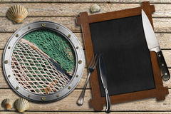 Seafood - Menu Template. Metal porthole with fishing net, empty blackboard, silver cutlery, kitchen knife and seashells on wooden background with sand. Template Royalty Free Stock Photo