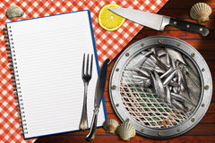 Seafood - Menu Template. Metal porthole with fishing net and fishes, kitchen knife with a slice of lemon and silver cutlery, empty notebook and seashells on Stock Photography