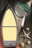 Seafood - Menu Template. Small boat with empty pages, metal porthole with fishing net, kitchen knife, seashells and starfish on wooden background with tablecloth Stock Photo
