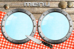 Seafood - Menu Template. Two empty metal portholes, kitchen knife and red checked tablecloth, template for recipes or seafood menu Royalty Free Stock Photography