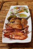 Seafood mix barbecue with salad on plate on bamboo table Stock Photos