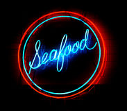 Seafood Neon Sign. Neon seafood sign against a brick wall Stock Photo