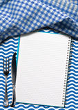 Seafood - Notebook with Blue Waves. Open notebook for recipes or fish menu on a background with blue and white waves, silver cutlery and blue and white checkered Royalty Free Stock Photography