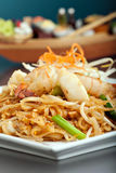 Seafood Pad Thai Dish. Of fried rice noodles on a square white plate with chopsticks and grated carrot garnish. Shallow depth of field Royalty Free Stock Photo