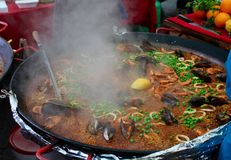 Seafood Paella. Close up of large frying bowl of seafood paella with mussells and shrimp prawns in an open market royalty free stock photo