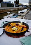 Seafood paella with glass of wine in seaside cafe,Spain Royalty Free Stock Images
