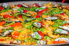 Seafood paella in a paella pan. It consists of shrimp, mussels, peas, beans and spices stock photo