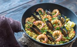 Seafood paella in the pan. On the wooden table stock images