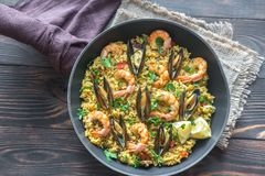 Seafood paella in the pan. On the wooden table royalty free stock images