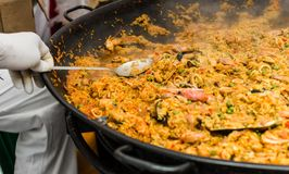 Seafood paella in a paella pan at a street food market. Seafood paella in a paella pan stock images