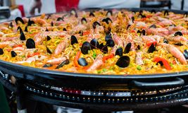 Seafood paella in a paella pan at a street food market. Seafood paella in a paella pan stock photography
