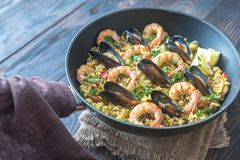 Seafood paella in the pan. On the wooden table stock photos