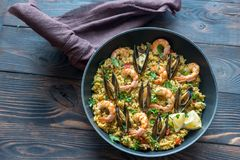 Seafood paella in the pan. On the wooden table stock photography