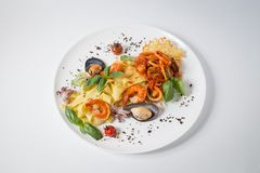 Seafood pasta with mussels, octopus, shrimps, tomatoes and green royalty free stock image