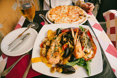 Seafood pasta, pizza and beer in Italy Stock Photography