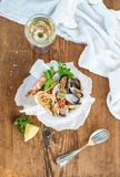 Seafood pasta. Spaghetti with clams and shrimps in bowl, glass of white wine over rustic wood background Royalty Free Stock Photo