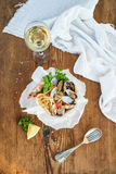 Seafood pasta. Spaghetti with clams and shrimps in bowl, glass of white wine over rustic wood background Stock Images