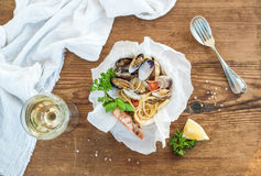 Seafood pasta. Spaghetti with clams and shrimps in bowl, glass of white wine Royalty Free Stock Images