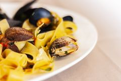 Seafood pasta spaghetti linguine wish mussels, clams, tomato sauce, fresh parmesan on the white plate in restaurant in Catania, Si royalty free stock images