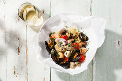 Seafood pasta and wine. Spaghetti with clams, prawns, sea scallops on white plate Stock Photography