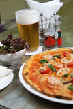 Seafood pizza with salad and beer Royalty Free Stock Photography