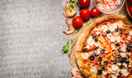 Seafood pizza with shrimp and tomatoes. On stone table. Stock Photos