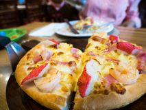 Seafood pizza topping whit Crab, shrimp and ham On a wooden tray. The background is restaurant.  Stock Images
