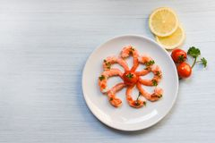 Seafood plate with shrimps prawns ocean gourmet dinner served on plate seafood cooked with ketchup. Herbs and spices on white wooden background stock images