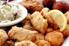 Seafood Platter. Fried seafood platter with fish, crab cakes, oysters, shrimp, hush puppies, cole slaw, and lemon slice Stock Photo