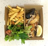 Seafood platter with chips & fresh raw salad. The mixed seafood includes deep fried fish fillet, green mussel and calamari. The meal is served in different Stock Images