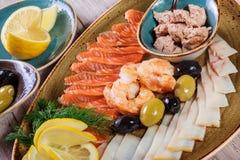 Seafood platter. Fresh cod liver, salmon, shrimp, slices fish fillet, decorated with herb. Lemon and olives on light wooden background. Mediterranean royalty free stock images