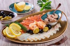Seafood platter. Fresh cod liver, salmon, shrimp, slices fish fillet, decorated with herb, lemon. And olives on light wooden background. Mediterranean stock photo