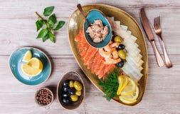 Seafood platter. Fresh cod liver, salmon, shrimp, slices fish fillet, decorated with herb, lemon and olives. On light wooden background. Mediterranean stock image