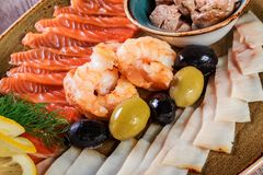 Seafood platter. Fresh cod liver, salmon, shrimp, slices fish fillet, decorated with herb, lemon and olives. On light wooden background. Mediterranean stock photos