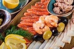 Seafood platter. Fresh cod liver, salmon, shrimp, slices fish fillet, decorated with herb,. Lemon and olives on light wooden background. Mediterranean stock photos