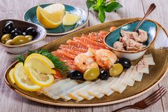 Seafood platter. Fresh cod liver, salmon, shrimp, slices fish fillet, decorated with herb, lemon and olives. On light wooden background. Mediterranean stock photography