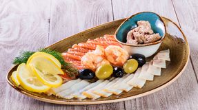 Seafood platter. Fresh cod liver, salmon, shrimp, slices fish fillet,decorated with herb on light wooden background Royalty Free Stock Photography
