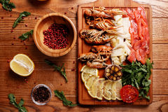 Seafood platter. Fresh crayfish, red and white pangasius fish fillet decorated with arugula, tomatoes, lemon, garlic and spice on a wooden board. Seafood platter Royalty Free Stock Photos