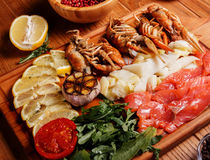 Seafood platter. Fresh crayfish, red and white pangasius fish fillet decorated with arugula, tomatoes, lemon, garlic and spice on a wooden board. Seafood platter Stock Images