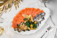 Seafood platter with salmon fillet, pangasius fish, herring, decorated with olives and lemon on marble background. Mediterranean appetizers, top view stock image