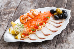 Seafood platter with salmon slice, pangasius fish, red caviar, shrimp, decorated with olives and lemon Stock Image