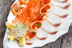 Seafood platter with salmon slice, pangasius fish, red caviar, shrimp, decorated with olives and lemon on wooden background Stock Photography