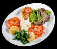 Seafood platter with salmon slice, pangasius fish, shrimp, decorated with lemon and greens on black background isolated.  royalty free stock images