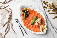 Seafood platter with salmon slice, pangasius fish, shrimp, decorated with olives and lemon on marble background. Mediterranean appetizers, top view royalty free stock images