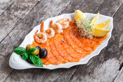 Seafood platter with salmon slice and shrimp, decorated with olives and lemon on wooden background close up Stock Photo
