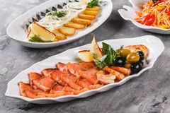 Seafood platter with salmon slice, shrimp, slices fish fillet, decorated with olives and lemon in plate over rustic background. Mediterranean appetizers royalty free stock photos