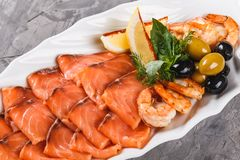 Seafood platter with salmon slice, shrimp, slices fish fillet, decorated with olives and lemon in plate over rustic background. Mediterranean appetizers royalty free stock image